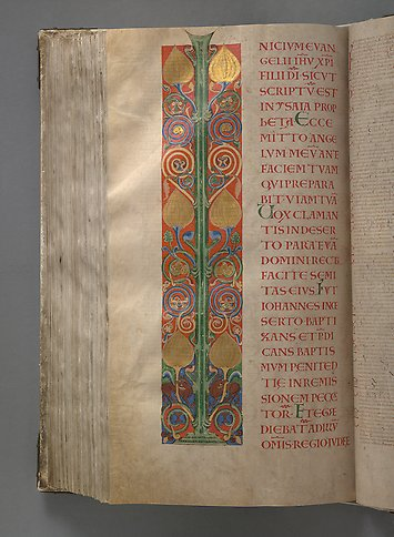 A book page with ornamentation in gold, green and red.