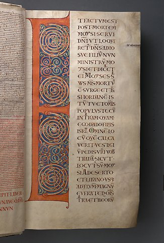 A book page with the letter E and colorful ornamentation.