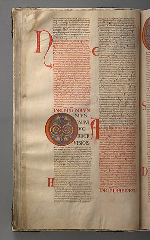 A book page with text and the initial o with colorful ornamentation.